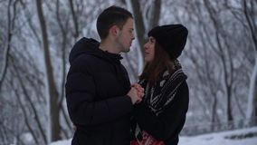 Conversa bonita da jovem mulher e do homem que olha nos olhos de cada um no parque do inverno sob a neve de queda O homem aquece  filme