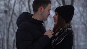 Conversa bonito da jovem mulher e do homem do retrato que olha nos olhos de cada um no parque do inverno O homem aquece as mãos d video estoque