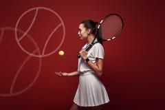 Conversa com seu raquet, jogo com seu coração Posição nova do jogador de tênis isolada sobre o fundo vermelho com uma raquete e imagem de stock