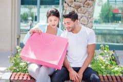 Conversa da compra Acople o assento em um banco e guardar a compra Fotografia de Stock Royalty Free