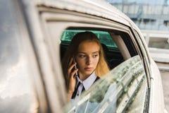Conversa da menina pelo telefone no dia chuvoso no carro imagem de stock