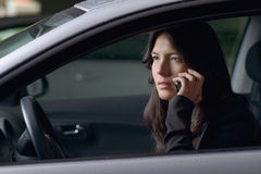 Conversa de assento do motorista da mulher em seu móbil Foto de Stock Royalty Free