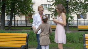 Conversa de dois amigos das mulheres no parque A menina corre até sua mãe e abraça-a filme