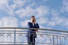 Conversa do chefe no telefone celular no céu azul Homem de negócios com smartphone Homem no terno formal em exterior ensolarado V Foto de Stock Royalty Free