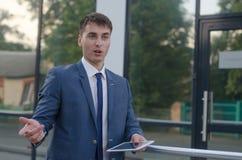 Conversa do homem de negócios com o portátil na mão esquerda Foto de Stock