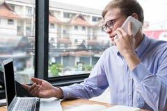 Conversa do homem de negócios no telefone celular no escritório o homem novo chama a manutenção programada imagens de stock