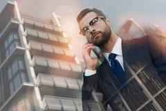 Conversa do negócio Homem de negócios novo seguro no terno que fala no telefone celular ao andar fora com arquitetura da cidade s fotografia de stock