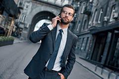 Conversa do negócio Homem novo considerável no terno completo que fala no telefone Vista colhida fotografia de stock