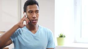Conversa do telefone, homem negro novo que atende à chamada video estoque
