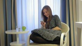 A conversa e a extremidade bonitas da mulher chamam pelo smartphone no assento da sala de hotel na cadeira video estoque