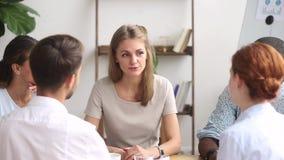 A conversa fêmea do gerente do mentor aos clientes diversos dos internos agita a mão filme