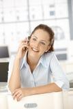 Conversa fêmea nova no assento móvel no escritório fotografia de stock royalty free