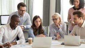 Conversa focalizada do grupo dos empregados que trabalha junto olhando o laptop imagens de stock