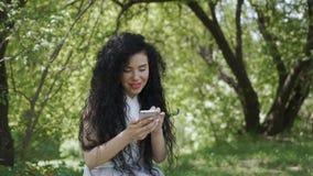 Conversa moreno bonita com os amigos pelo telefone no jardim do verão filme