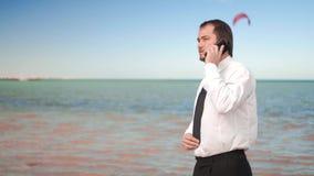 Conversa nova do homem de neg?cios no telefone celular perto do mar video estoque