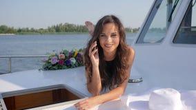 Conversa telefônica da jovem mulher no iate da plataforma no resto do verão filme