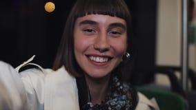 Conversa video da jovem mulher atrativa, espiando Mulher que acena na câmera ao sentar-se no transporte público fim vídeos de arquivo