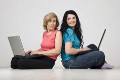 Conversación de dos mujeres usando la computadora portátil Fotografía de archivo libre de regalías