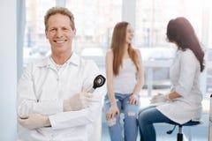 Conversación de goce paciente joven divertida con el doctor en el hospital Fotografía de archivo