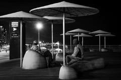 Conversación de los amigos en parque de la ciudad en la noche Fotografía de archivo