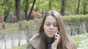 Conversación emocional sobre el smartphone de una mujer joven hermosa en un parque de atracciones de la ciudad metrajes
