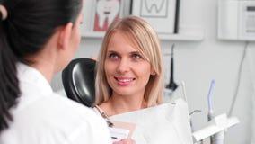 Conversación entre la mujer y el dentista sonrientes en la clínica del dentista almacen de metraje de vídeo