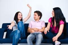 Conversación feliz de los amigos sobre el sofá Imagen de archivo