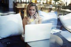 Conversación que habla de la mujer hermosa feliz sobre el teléfono móvil mientras que teniendo rotura de trabajo en restaurante m Foto de archivo libre de regalías