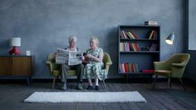 Conversación seria de pares mayores la esposa está viendo TV, marido lee el periódico almacen de metraje de vídeo