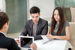 Conversación seria Hombre de negocios de tres jóvenes que se sienta en el tabl Imagen de archivo libre de regalías