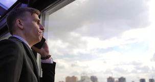 Conversación telefónica del hombre de negocios Un hombre joven se coloca en un traje gris en la oficina cerca de la ventana y hab metrajes
