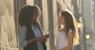 Conversating engraçado de dois estudantes de sorriso de encantamento na rua A menina está corrigindo o cabelo filme