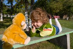 Conversation. The little girl lays on a bench and listens to the toy monkey Stock Images