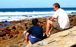 Conversation. Man and child sitting on rocks having a conversation Stock Image