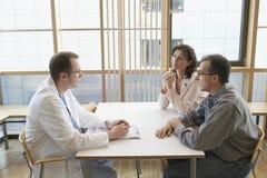在书桌的In Conversation With A医生夫妇 库存照片