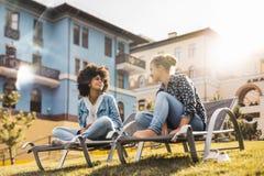 Conversation amicale de deux filles de différentes courses extérieures Photos stock