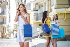 Conversation avec son mari à son téléphone portable Trois filles h Photos stock