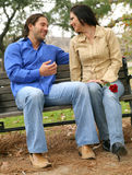 Conversation On Bench. Happy couple are talking in park. the woman holding red rose from the man royalty free stock image
