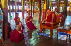 Conversation between Buddhist Monks, Ywama, Inle Lake, Myanmar. YWAMA, MYANMAR - FEBRUARY 18, 2018: Young boys - samaneras novice monks have conversation and Royalty Free Stock Photos