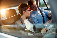 Conversation of business people in driving car. Conversation of two business people in driving car Stock Images