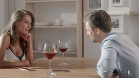 Conversation in cafe between woman and man, people sits at the table, hold glasses of wine in their hands and talk stock video footage