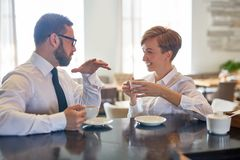 Conversation in cafe. Two confident entrepreneurs having conversation by cup of coffee in cafe Stock Photography