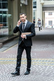 Conversation with the client. Confident businessman in formal suit talking on a cell phone royalty free stock image