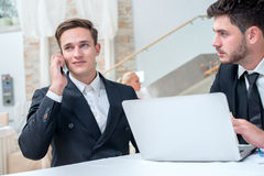 Conversation with the client. Two successful and confident busin. Essman sitting at the table in a business office in full costume in the office and working at a Royalty Free Stock Images