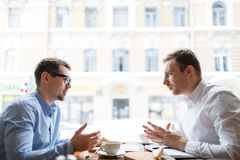 Conversation of co-workers. Young analysts having conversation by business lunch in cafe Stock Photo