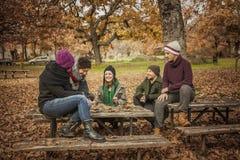 Conversation d'amis en parc complètement des feuilles Photographie stock libre de droits
