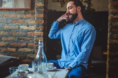 Conversation de téléphone portable d'imitation de hippie dans un café image libre de droits
