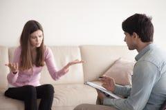 Conversation entre le psychologue masculin et le jeune patient féminin, image stock