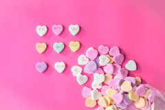 Conversation hearts on a pink background. Candy conversation hearts spilling out on a pink background for Valentine`s Day royalty free stock photos