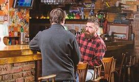 Conversation int?ressante Homme barbu brutal de hippie d?penser des loisirs avec l'ami au compteur de barre Hommes d?tendant ? la photo libre de droits